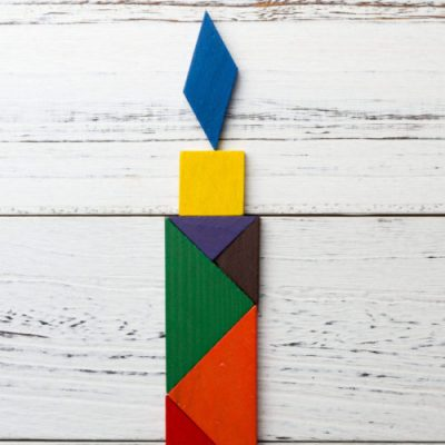 wooden tangram in a candle shape with copy space